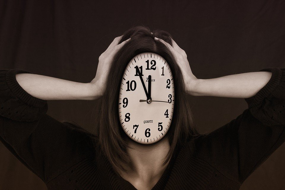 Woman holding a large clock in front of her face