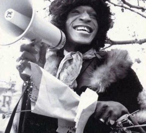 A black and white photo of Marsha P. Johnson at a protest, wearing a fur coat and holding a megaphone in one hand and a bouquet of flowers in the other. She is smiling widely.