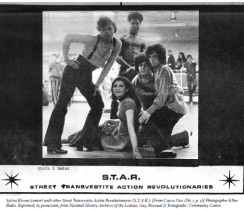 A black and white photograph showing Sylvia Rivera surrounded by four other visibly queer and gender nonconforming people, posed for a photograph for the queer magazine, Come Out.