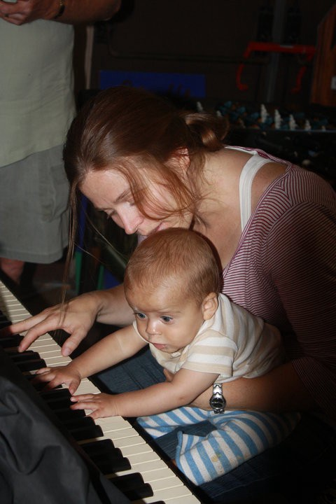 Photo of a mother and very young son (9 months) at the piano together. Her hair is sandy brown, pulled back, with strands falling across her face and down toward the piano. Her son's eyes bulge out as he grasps for the instrument. One of her hands holds him. The other touches the keys. Both of the baby's hands are on the white keys.