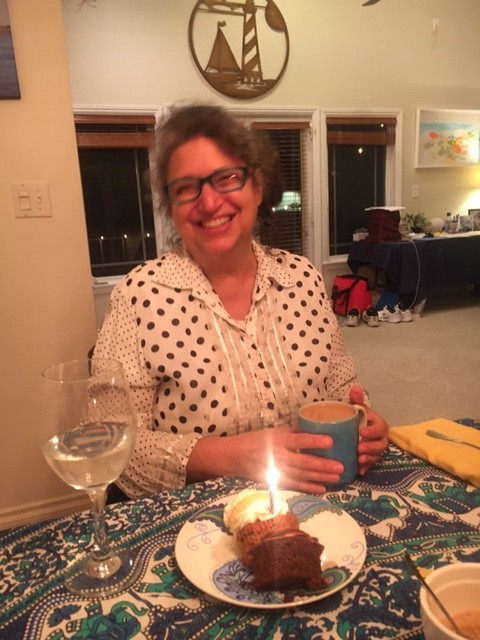 Author in white blouse with black polka-dots, wearing glasses, smiling, holding mu, sitting at table in back of cupcake with candle on it.