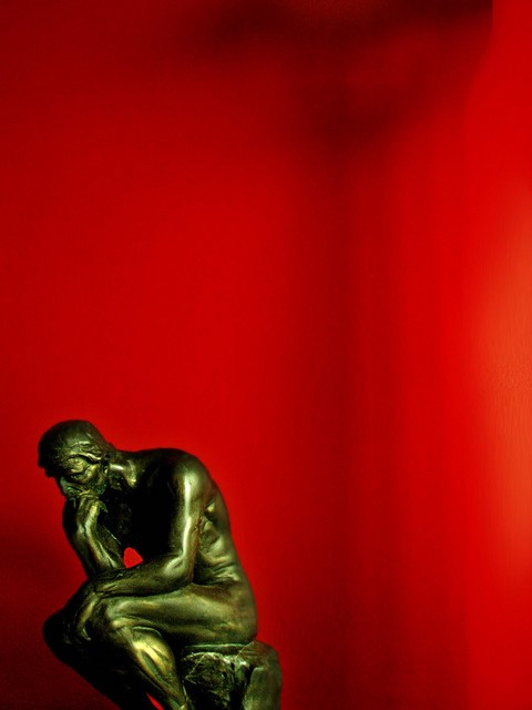 bronze statue in thinking pose with a red background