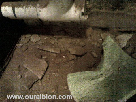 Rubble from the wall lies on the floor, underneath where the sink should be.