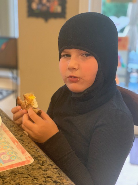 Boy wearing black ski mask and black t-shirt. Looking at camera and eating an egg-in-the-hole breakfast sandwich.