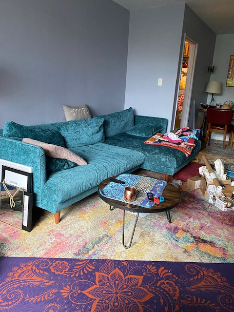 A large turquoise colored sectional with light blue walls behind it. There's a small round coffee table in front of the couch, un-hung pictures on one side of it, and a pile of opened boxes on the other side.
