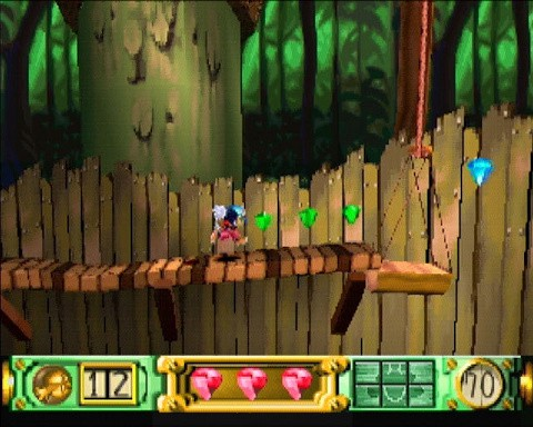 A screenshot from the game showing Klonoa running across a wooden platform in a forest area, collecting green and blue gems that are floating in midair.