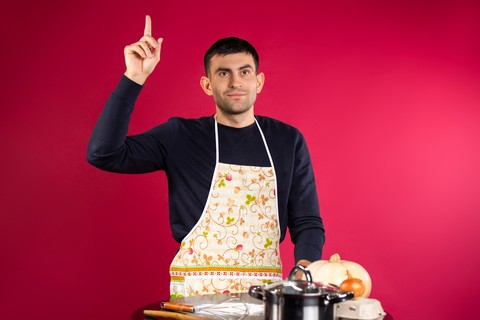 Man with cooking ingredients, wearing an apron, with his finger in the air
