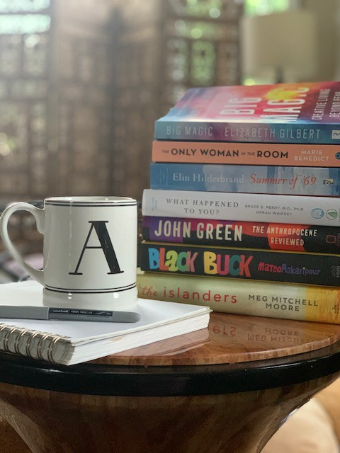 """Picture of coffee cup with """"A"""" on it, sitting on journal with pen. Stack of seven books are stacked in the background."""