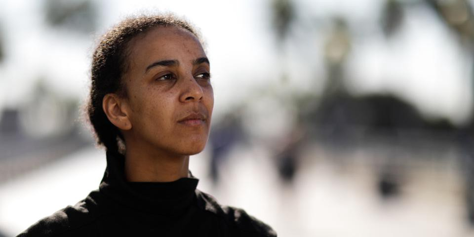 Dr. Timnit Gebru, wearing a black turtle neck and looking off to the side.
