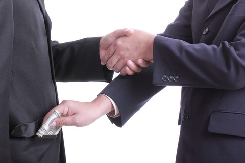 Two business men shaking hands, one is bribing the other.