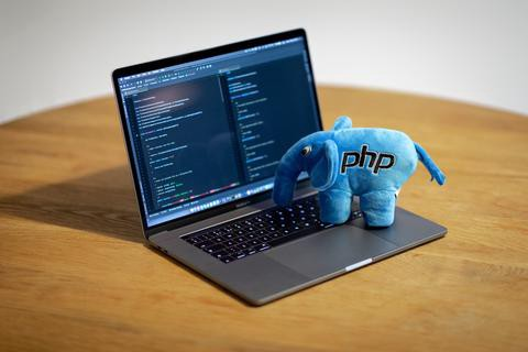 Image of a PHP stuffed elephant doll sitting on a laptop