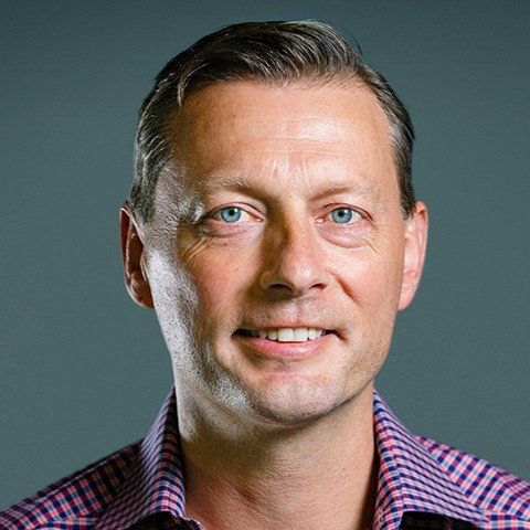 Color photo of Eric Wrobel, a White man with blue eyes and plaid shirt, Head of Product at Blend.