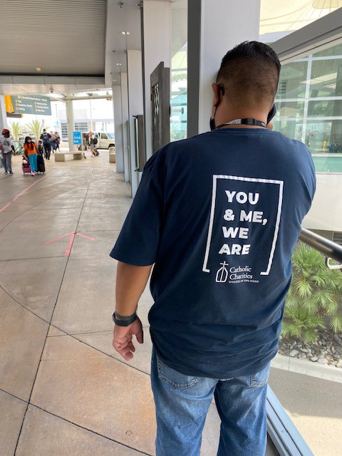 """A Catholic Charities worker wears a t-shirt that says """"You & Me, We Are"""" at the San Diego Airport."""