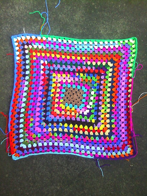 A crochet granny square made from yarn scraps