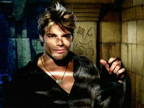 Young Ricki Martin wearing a long sleeved shirt and leather necklace, staring seriously and handsomely beyond the camera