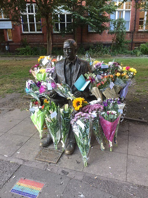 A statue of Alan Turing sitting on a bench surrounded by bouquets of flowers