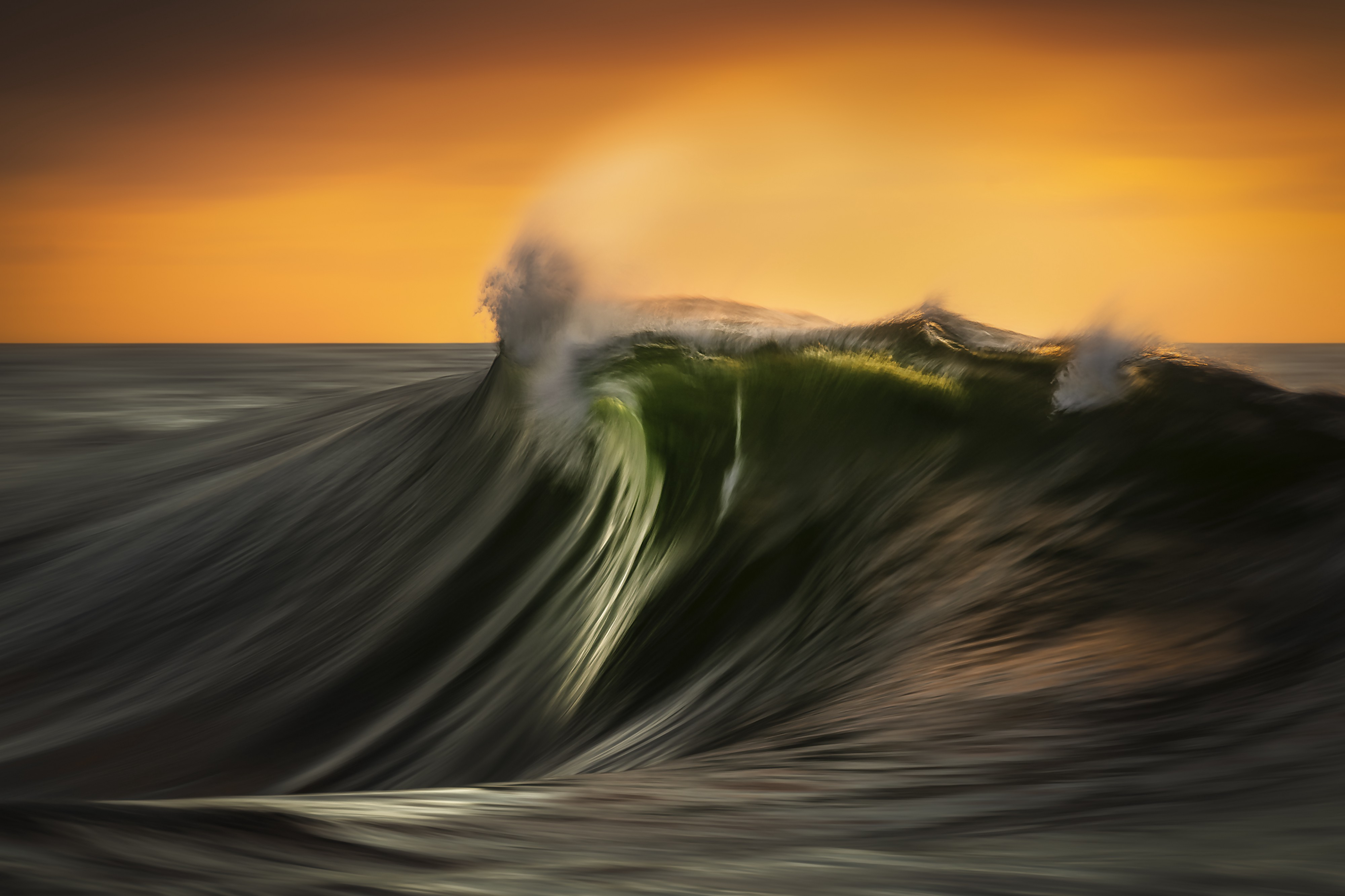 A large green wave with an orange sky in the background