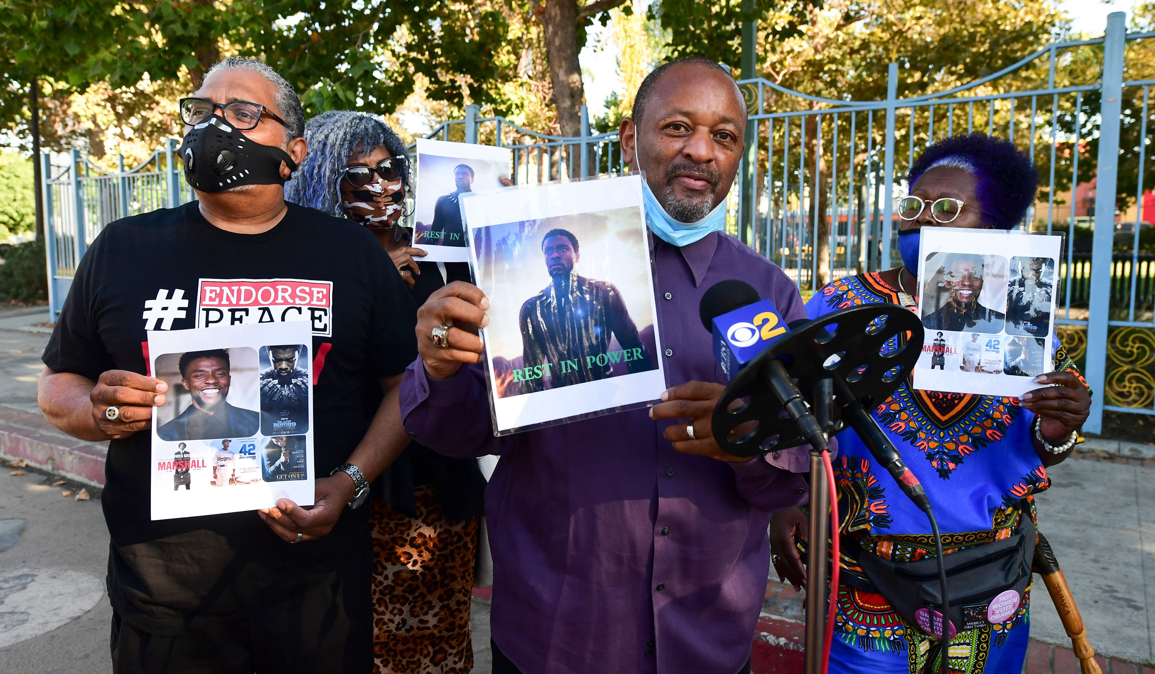 Photographs of the late actor and producer Chadwick Boseman are held during a vigil by fans.