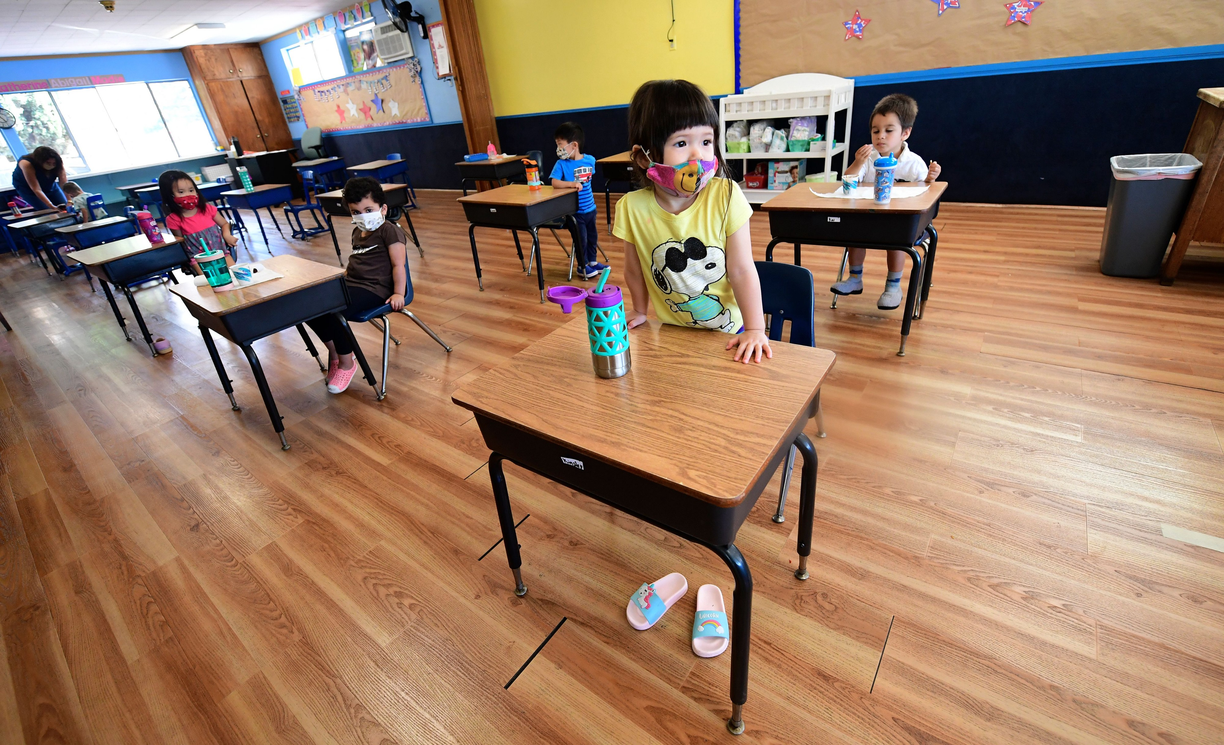 Children in a pre-school class wear masks and sit at desks spaced apart as per coronavirus guidelines during summer school.