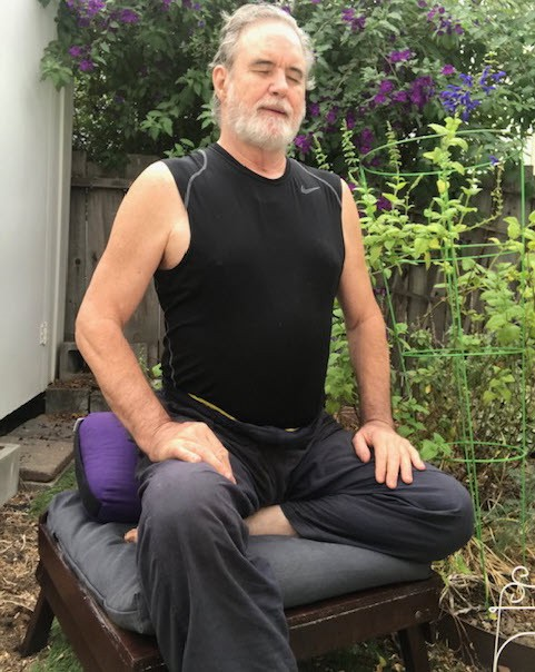 The author meditating on his bench in the garden, with a huge smile.
