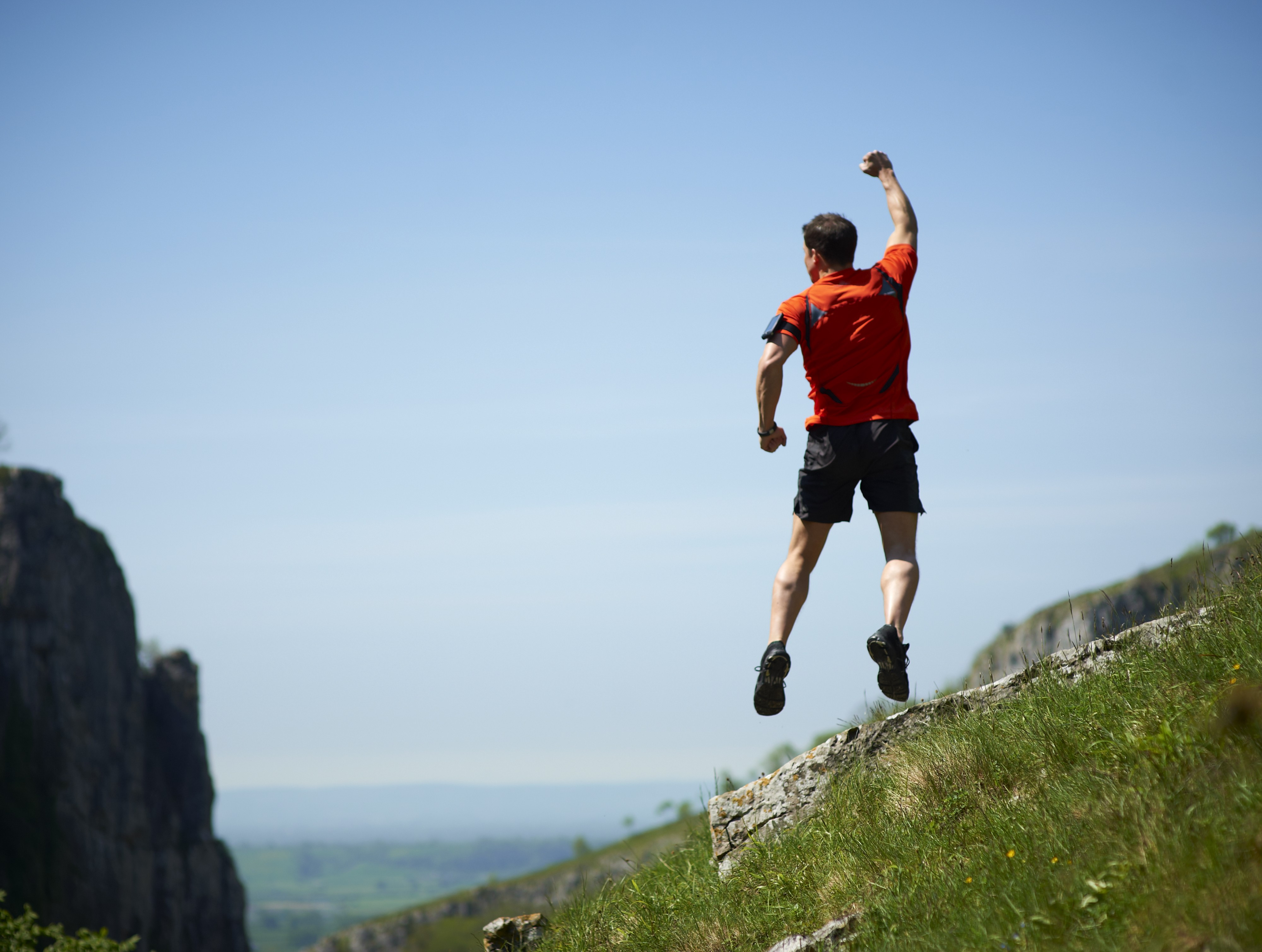 A male mountain runner is jumping up and punching the air.