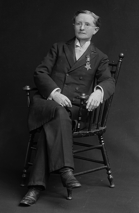 Photo of Mary Edwards Walker seated in a chair wearing a suit and medal of honor