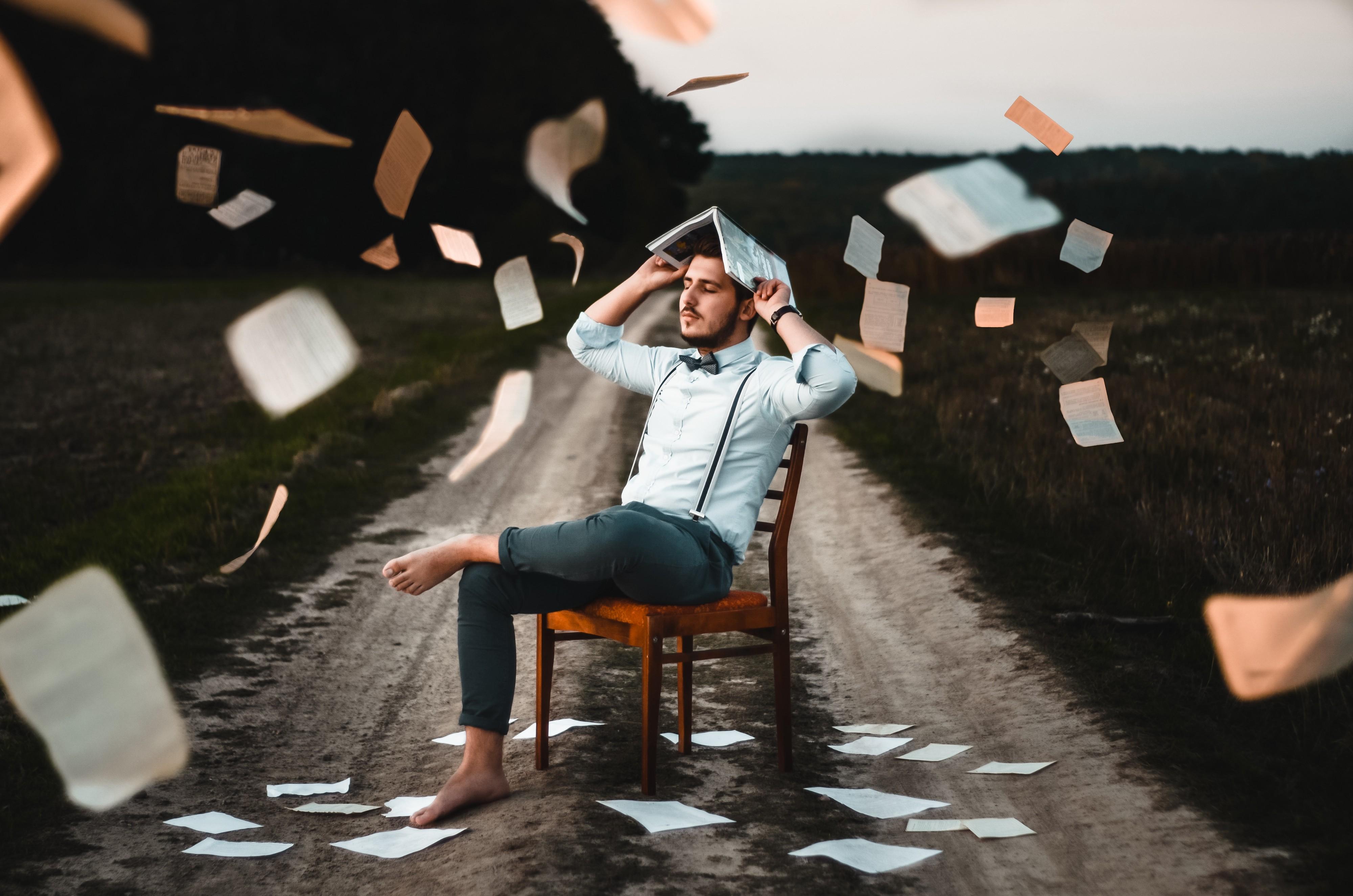 A man sitting alone surrounded by paper