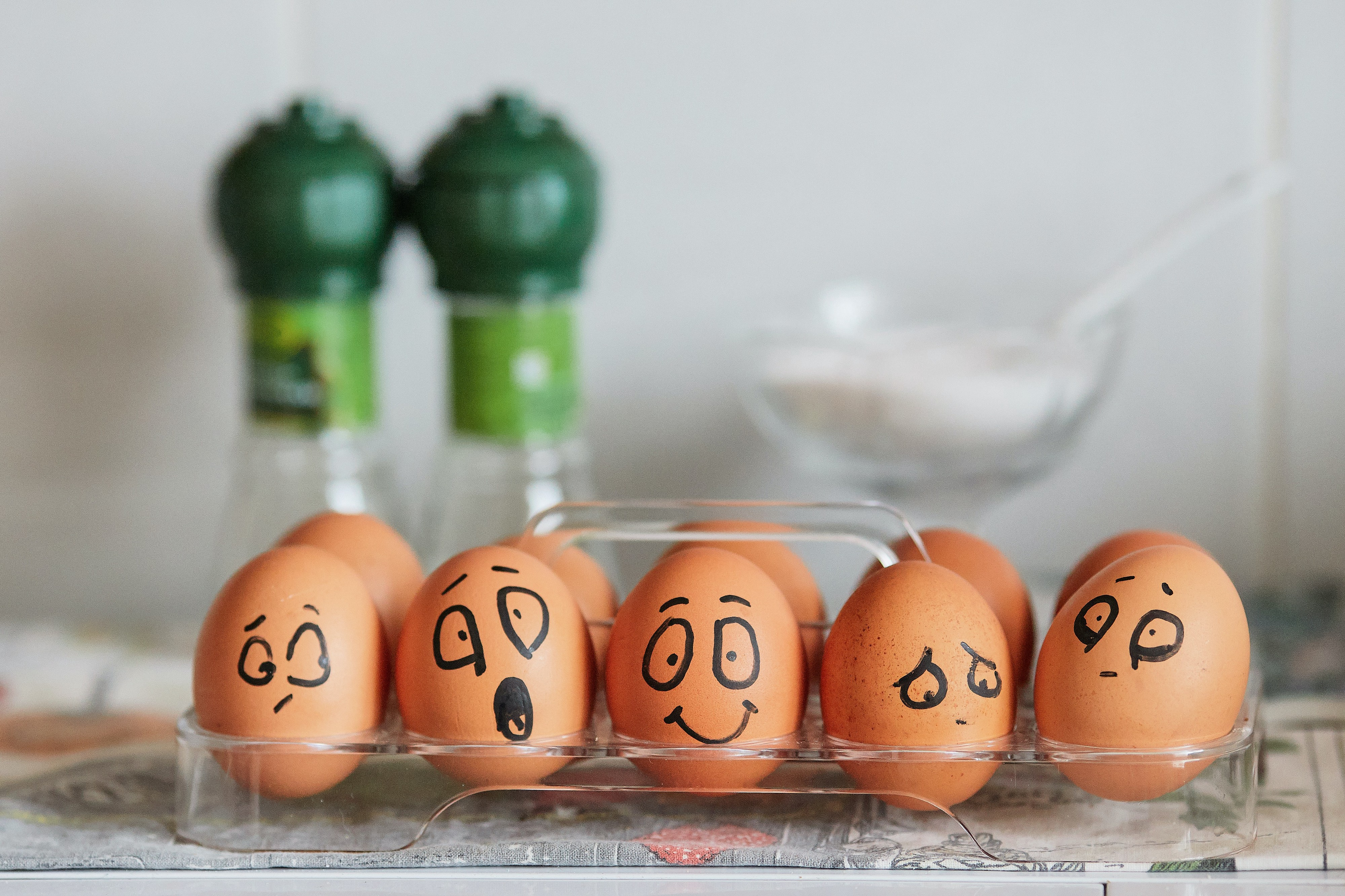 Eggs with drawn-on faces displaying different emotions. From left to right: indifference, surprise, happiness, sadness, fear.