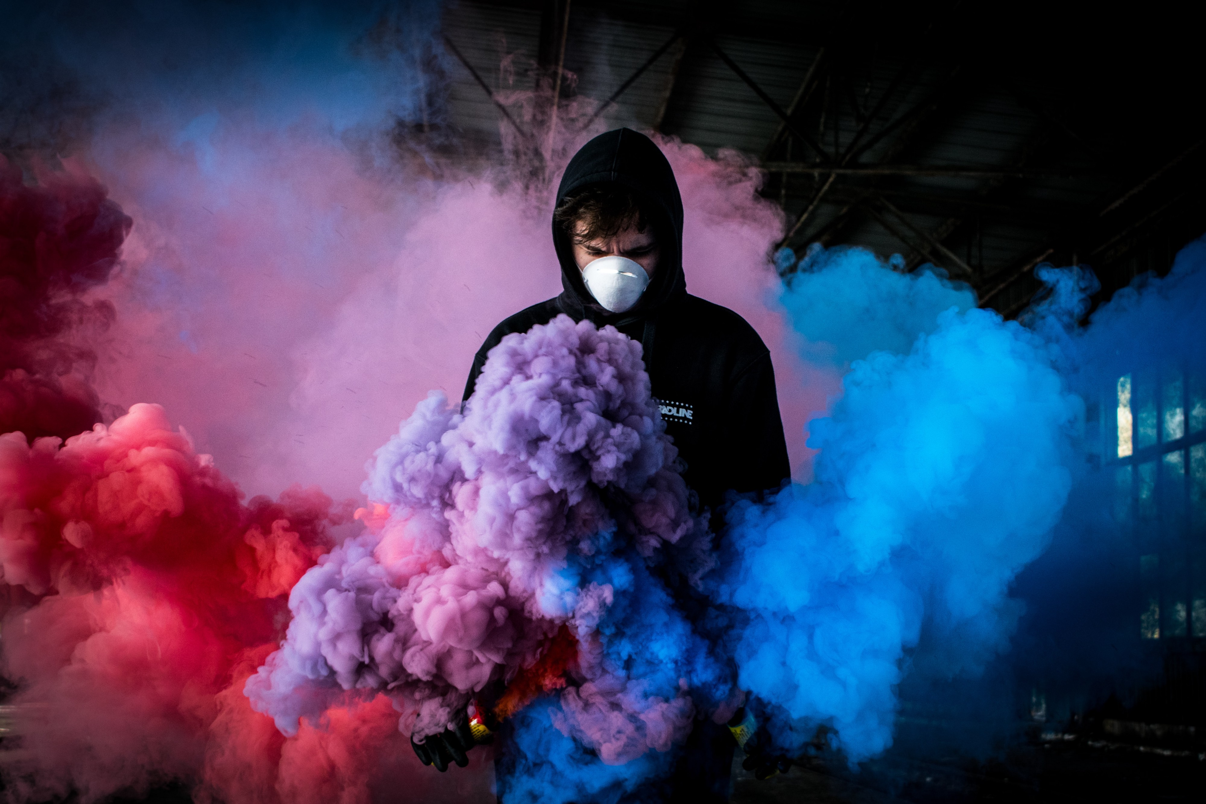 treated—a figure in a hoodie and mask moving through clouds of colorful smoke.