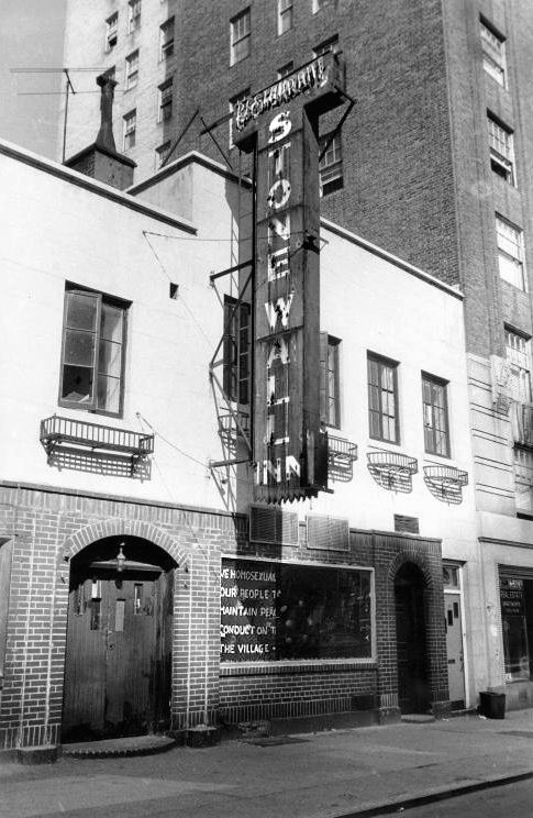 An antique photograph of the Stonewall Inn in daylight. The photo is in black and white. A neon sign displaying the name of the Inn hangs on the front of the two story building. The street below is empty.