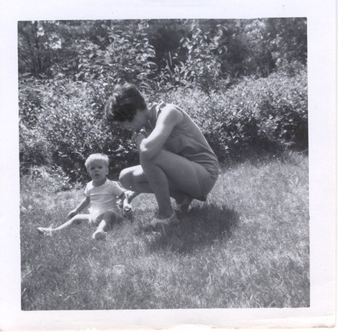 A photo of me as a young boy sitting on the grass with his mother. I'm wearing sandals.