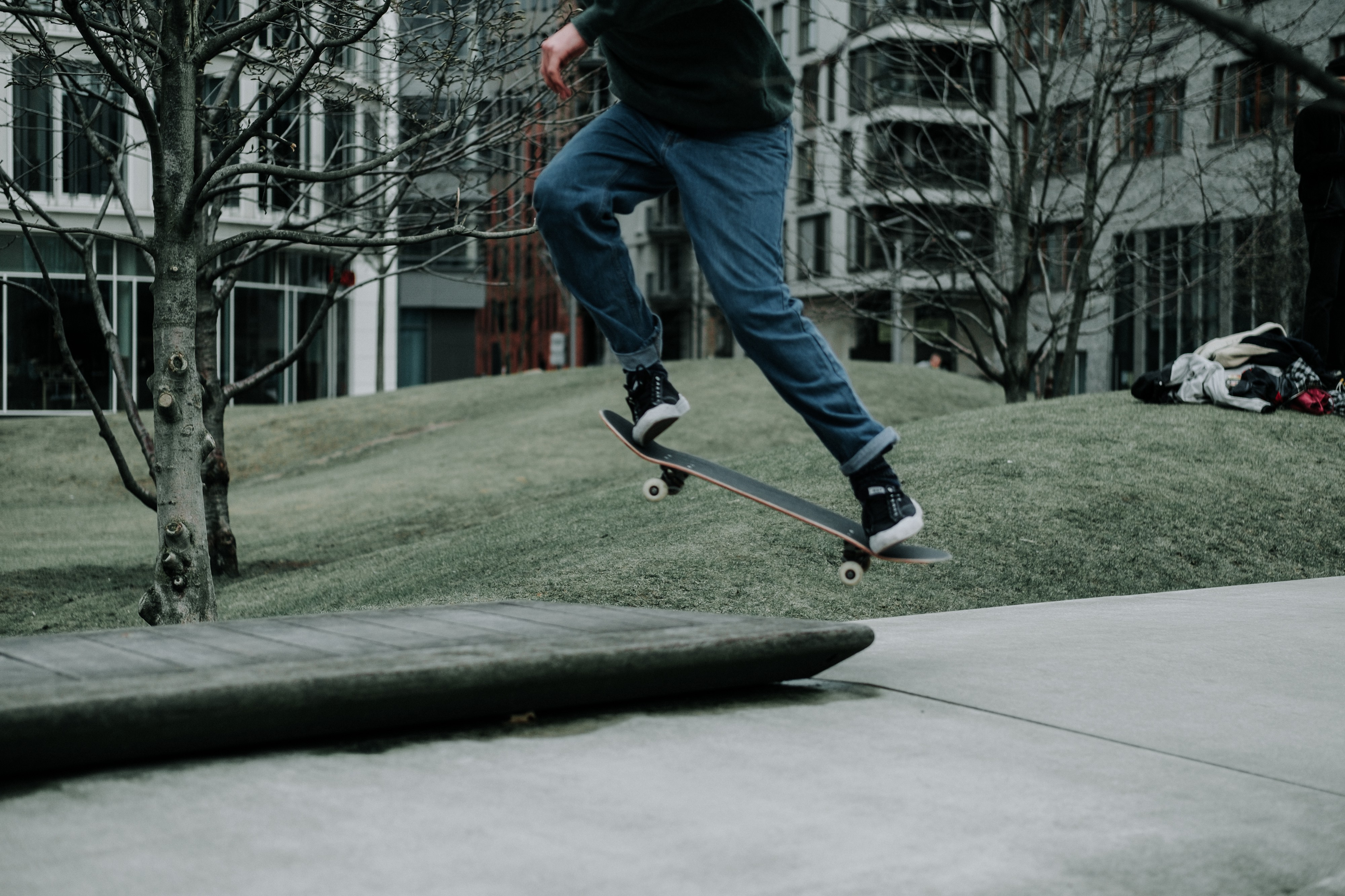 Low view of a teen doing a jump on a skateboard on the sidewalk.