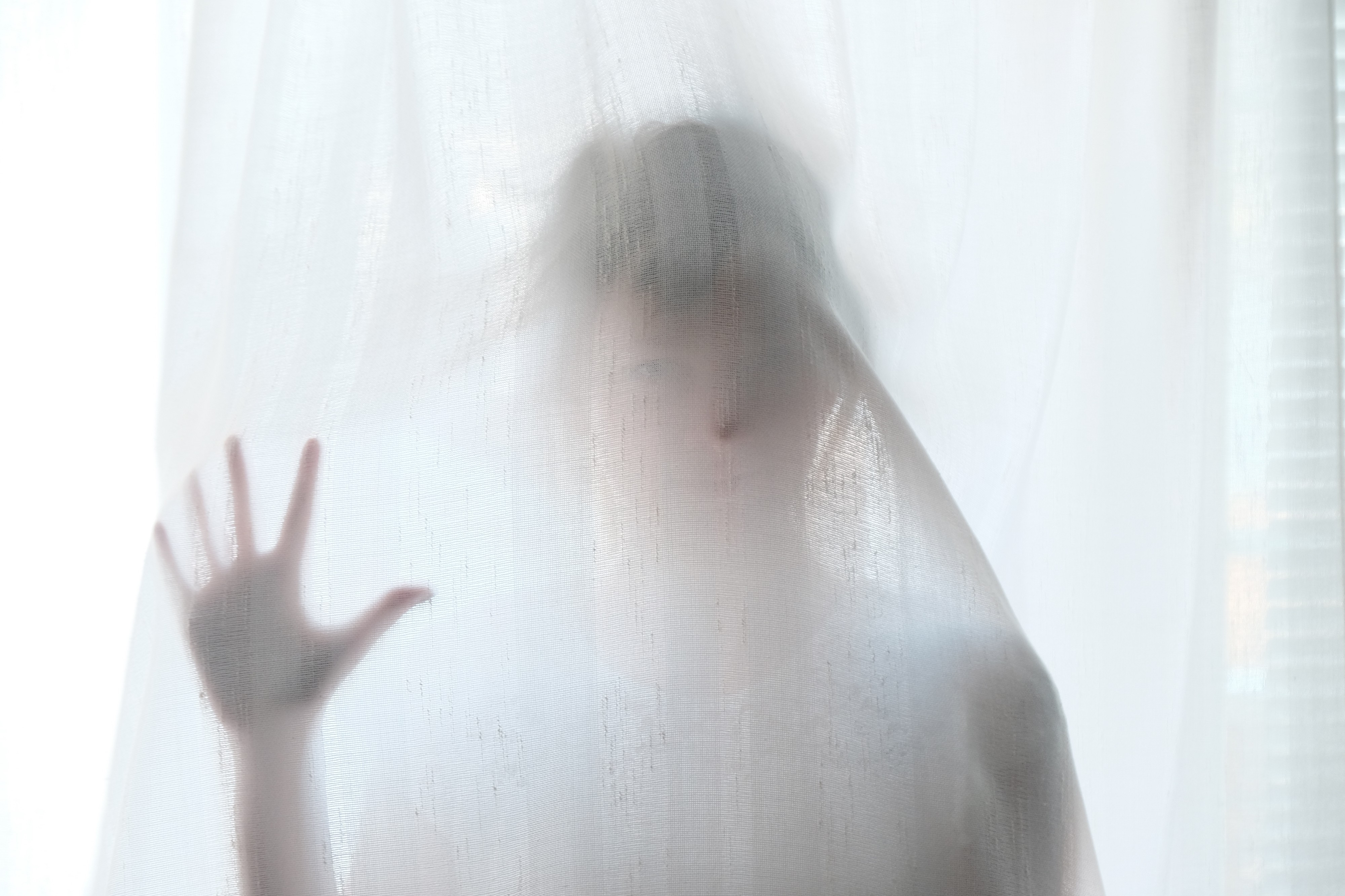 a shadowed figure behind a curtain raising a hand up. It looks to be a ghost or a phantom.