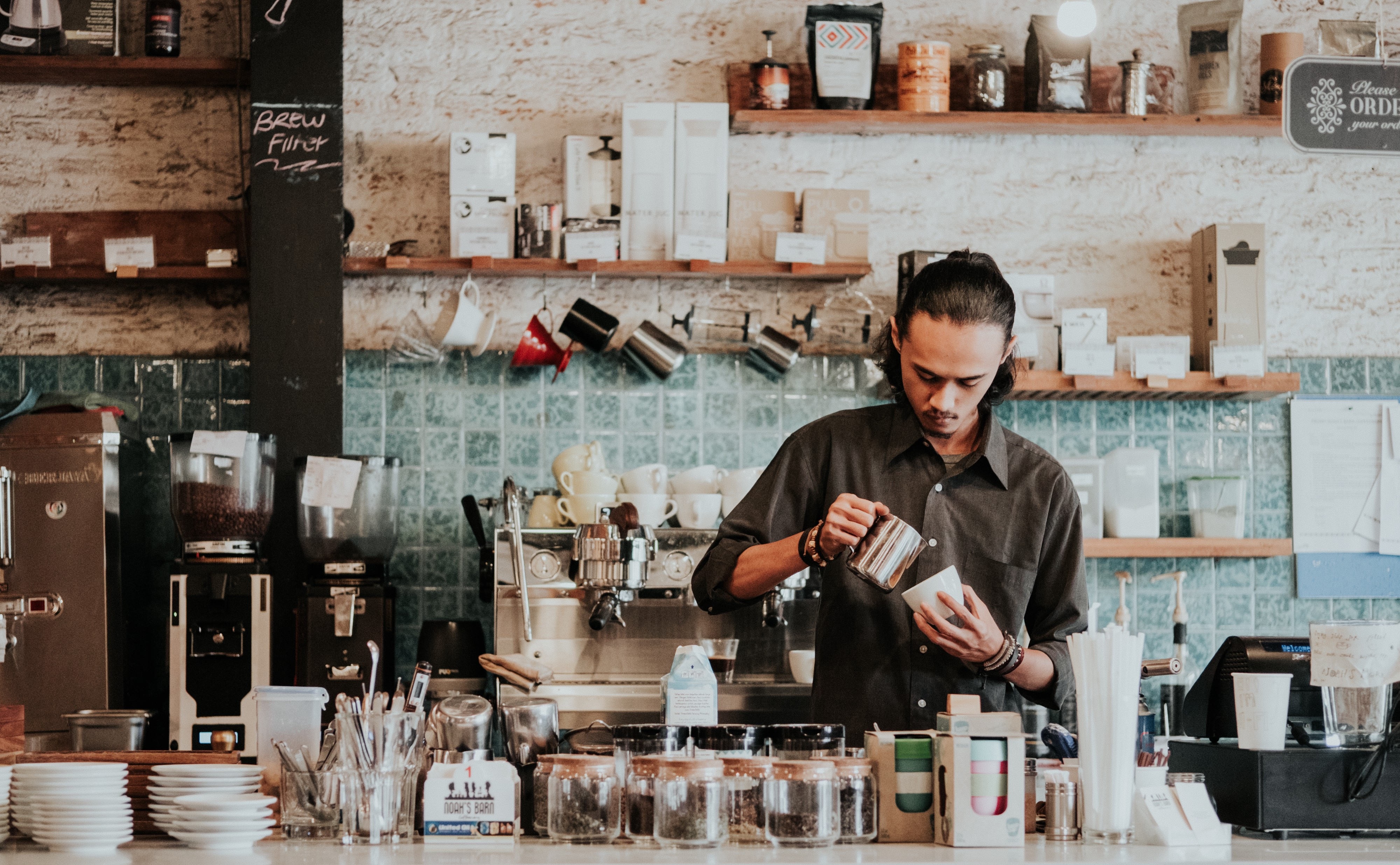 A barista makes a luxury coffee in a modern coffee shop