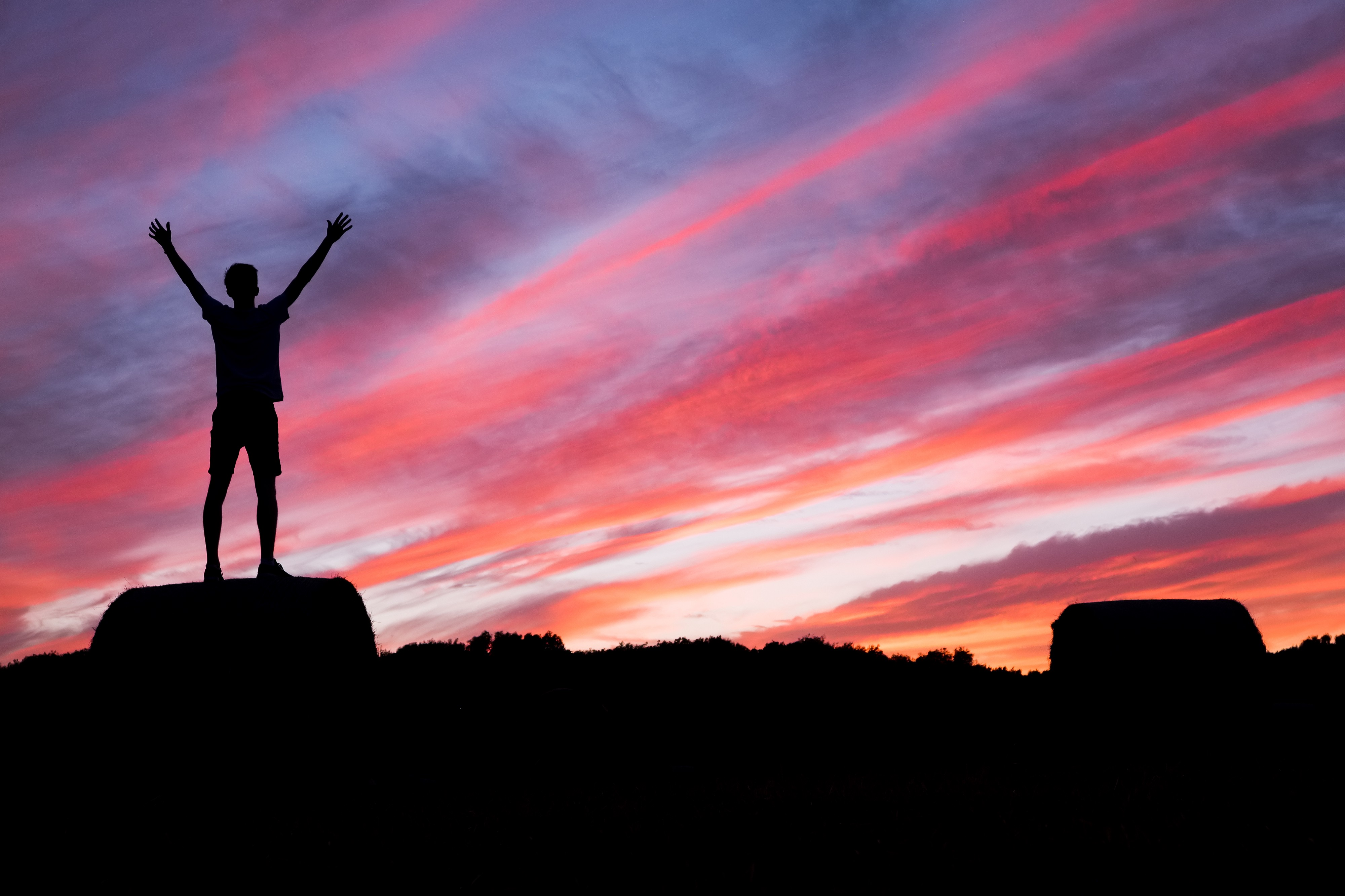 A man raises his arms in triumph while standing on a large rock and looking at a colorful sunset