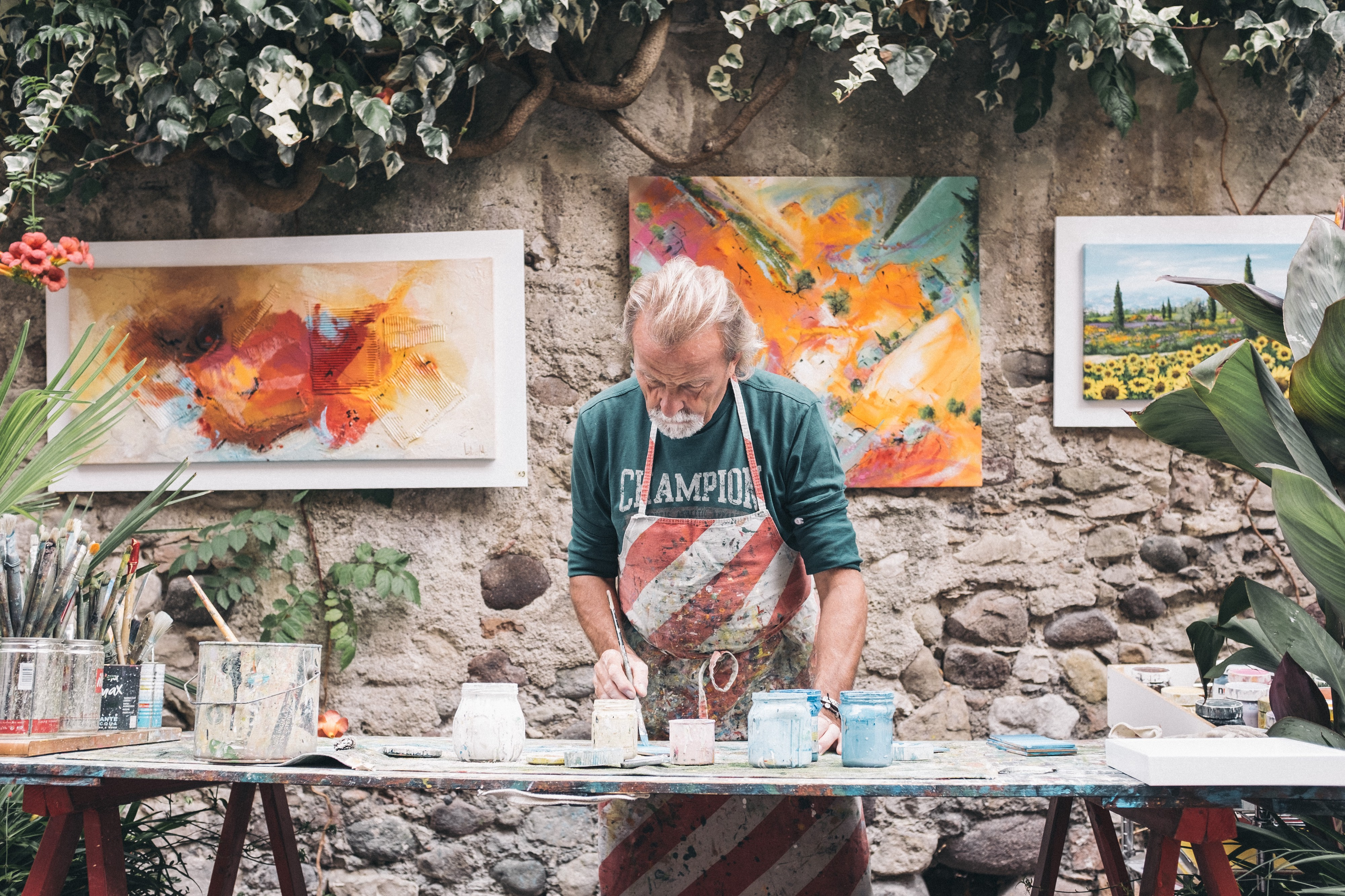 Man painting pottery outside