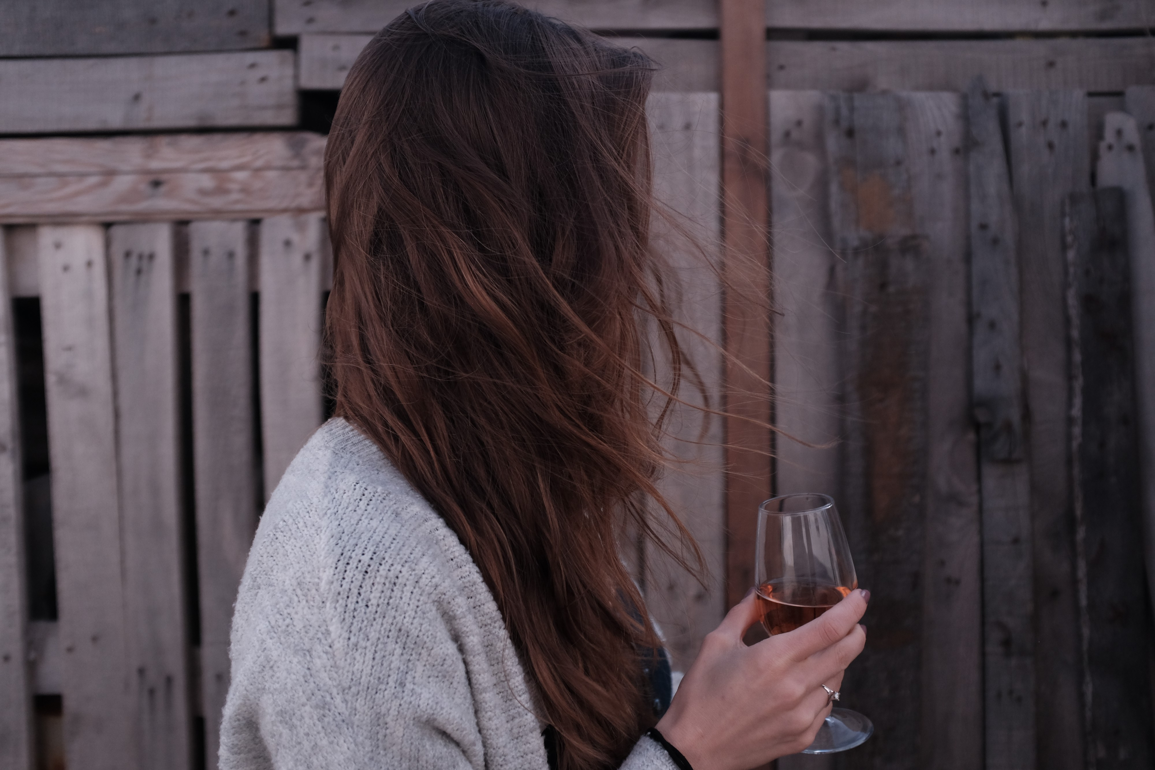 Side profile of a white woman holding a glass of wine, with her long brown hair obscuring her face.