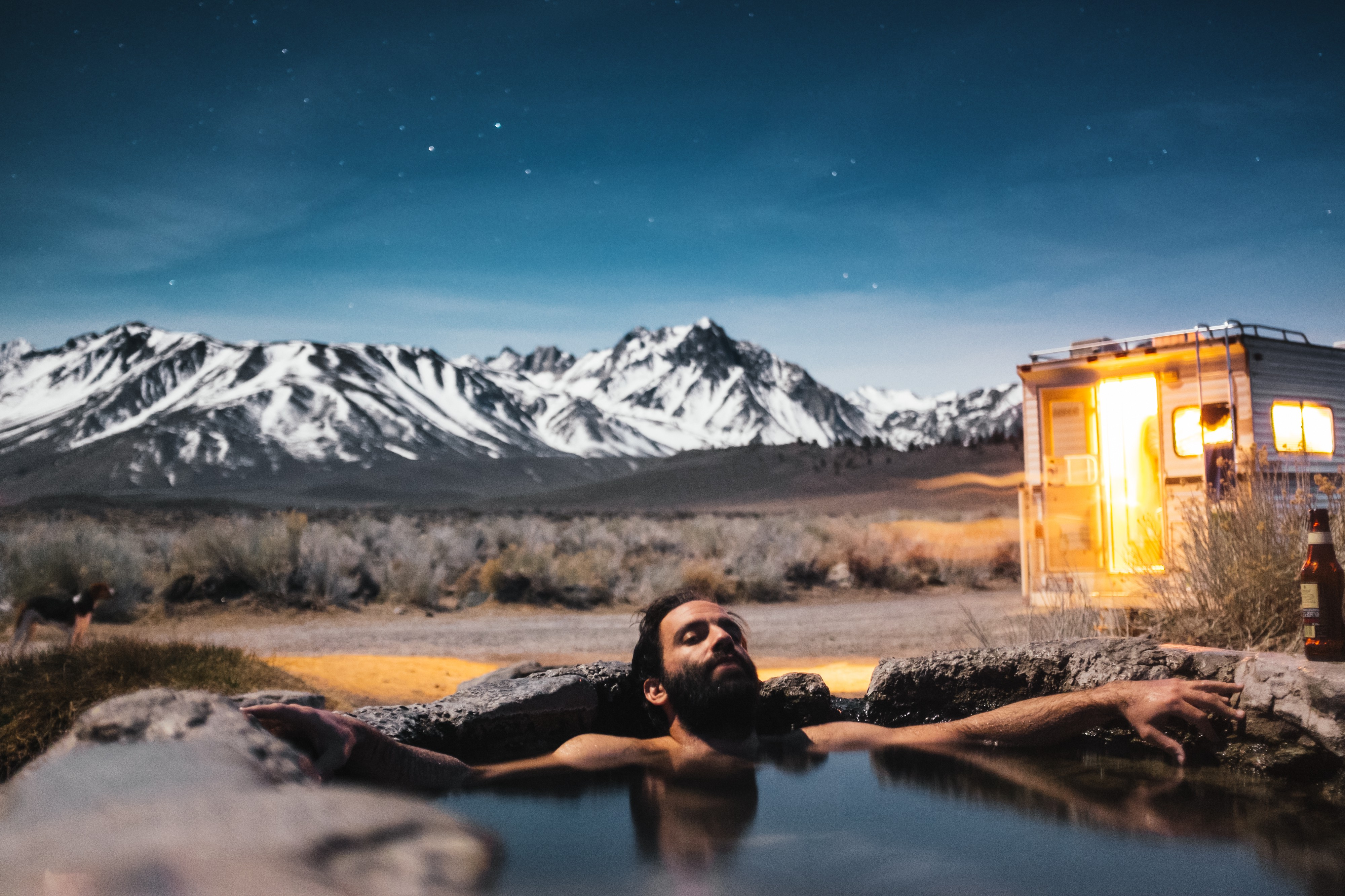 Man in hot tub at night with a beautiful view.