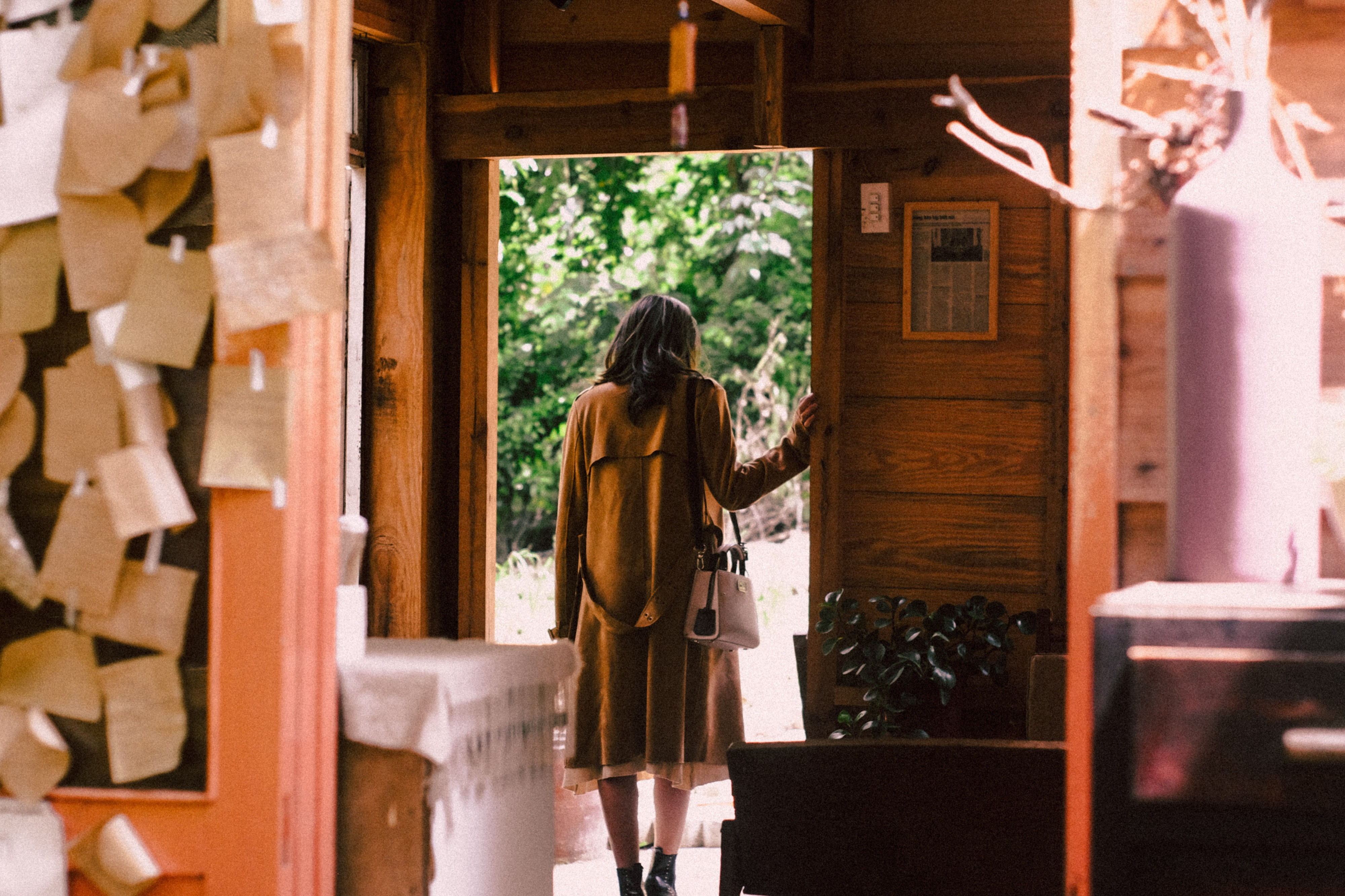 Woman about to leave an old house full of memories, paper and old items
