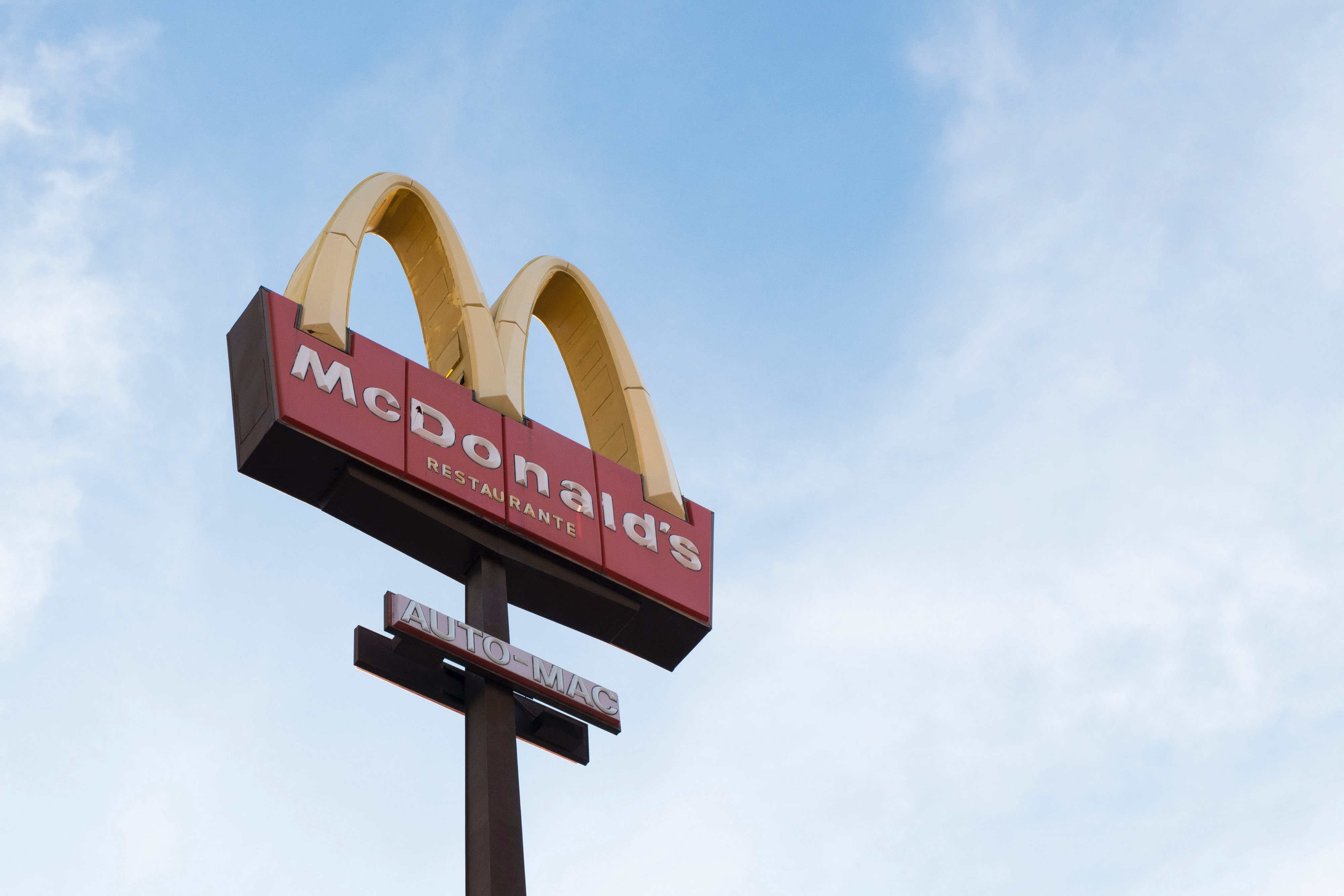A view towards a cloudy, blue sky showing a lone yellow and red sign for McDonalds