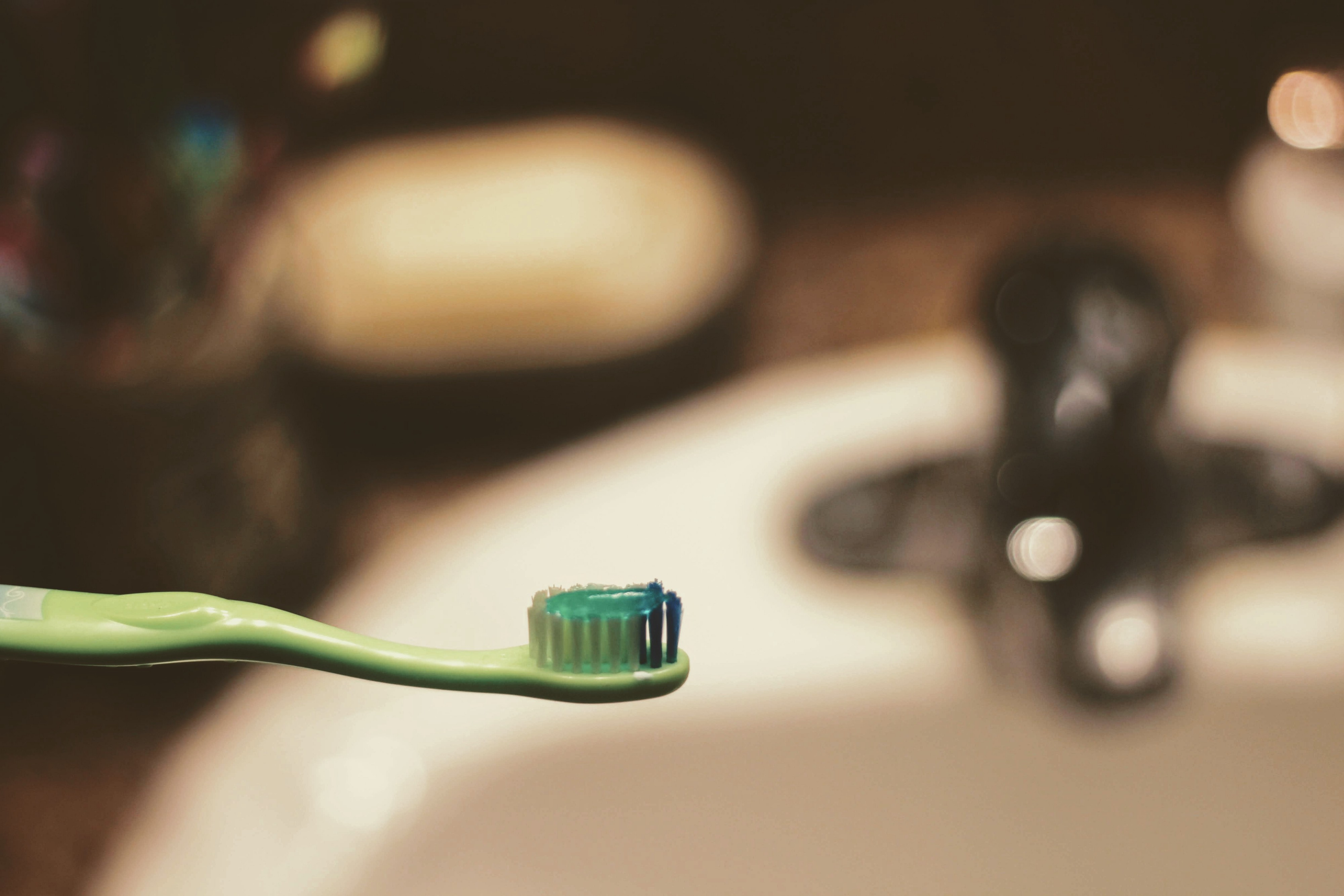 Closeup of a green toothbrush, with an out-of-focus sink in background.