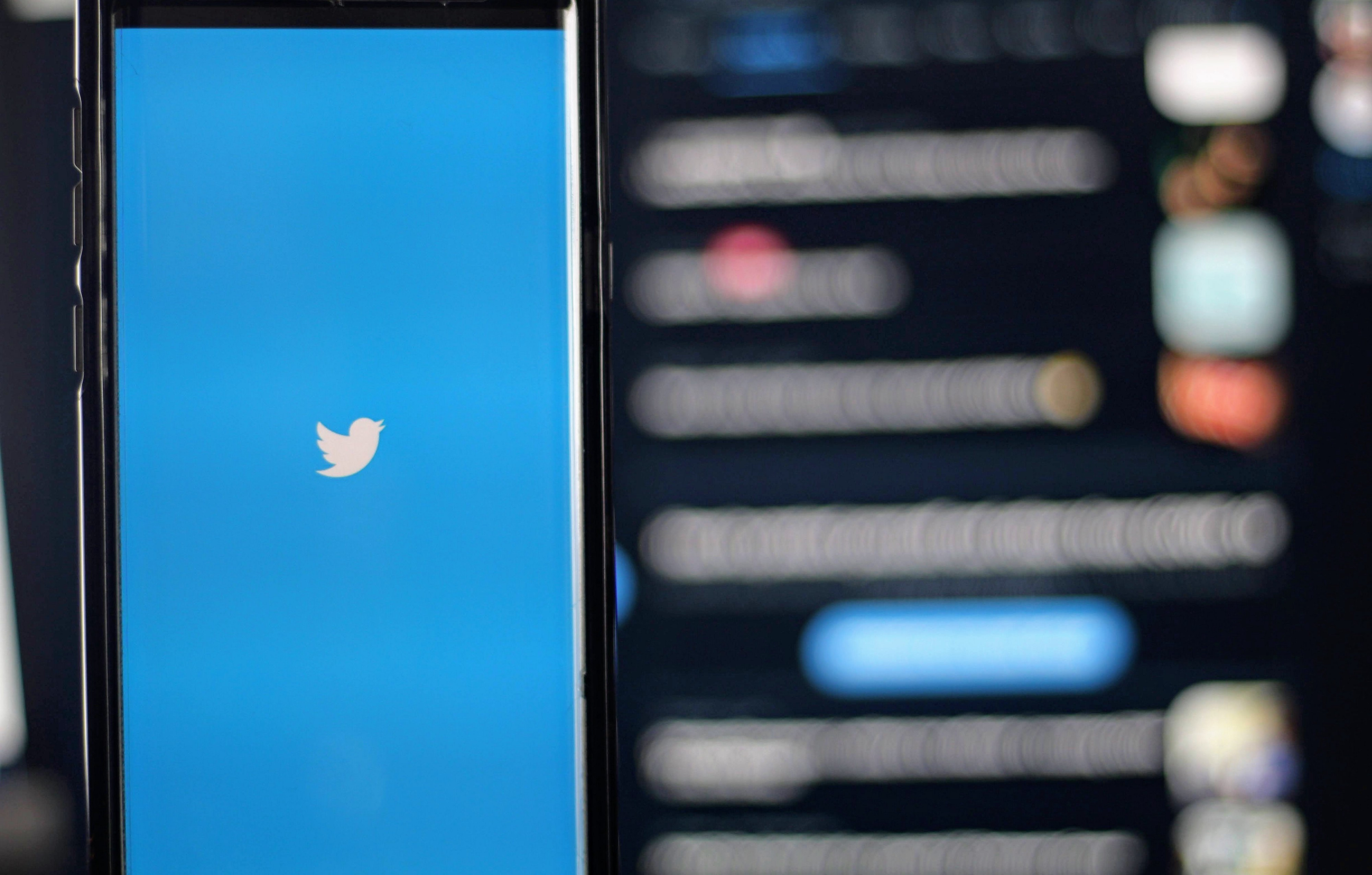 A mobile phone shows the Twitter app with a blurred screen behind it with various posts.