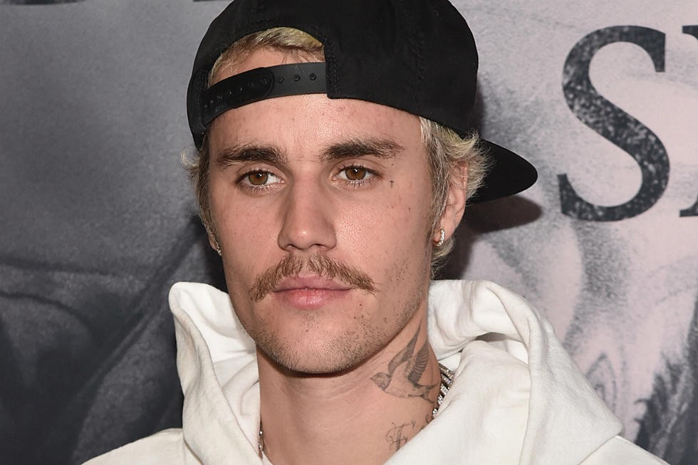 Justin Bieber with his mustache and bleach blond hair in a white hoodie