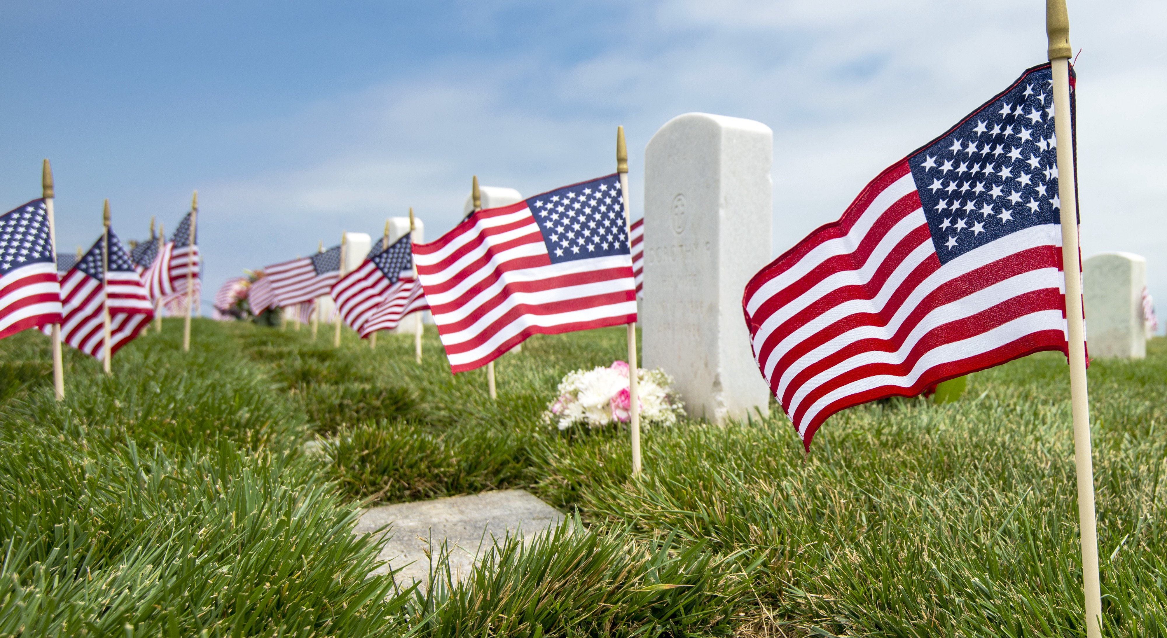A color photo shows a row of white marble military-style headstones, each decorated with a miniature U.S. flag sticking out of the ground in front of it.