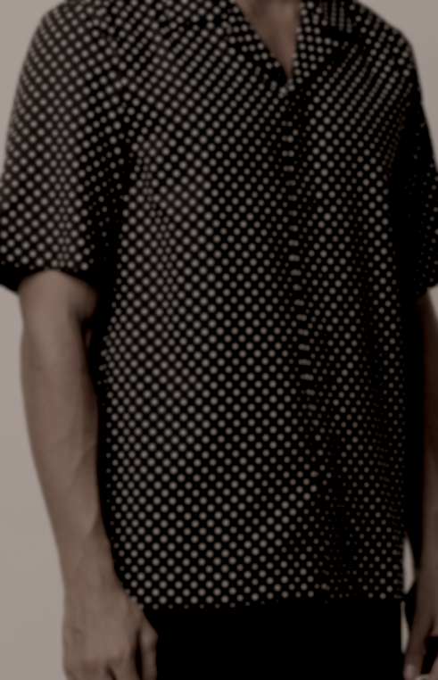 zoomed in, slightly blurry picture of man wearing a loose-fitting black shirt with small white polka dots, focus on torso