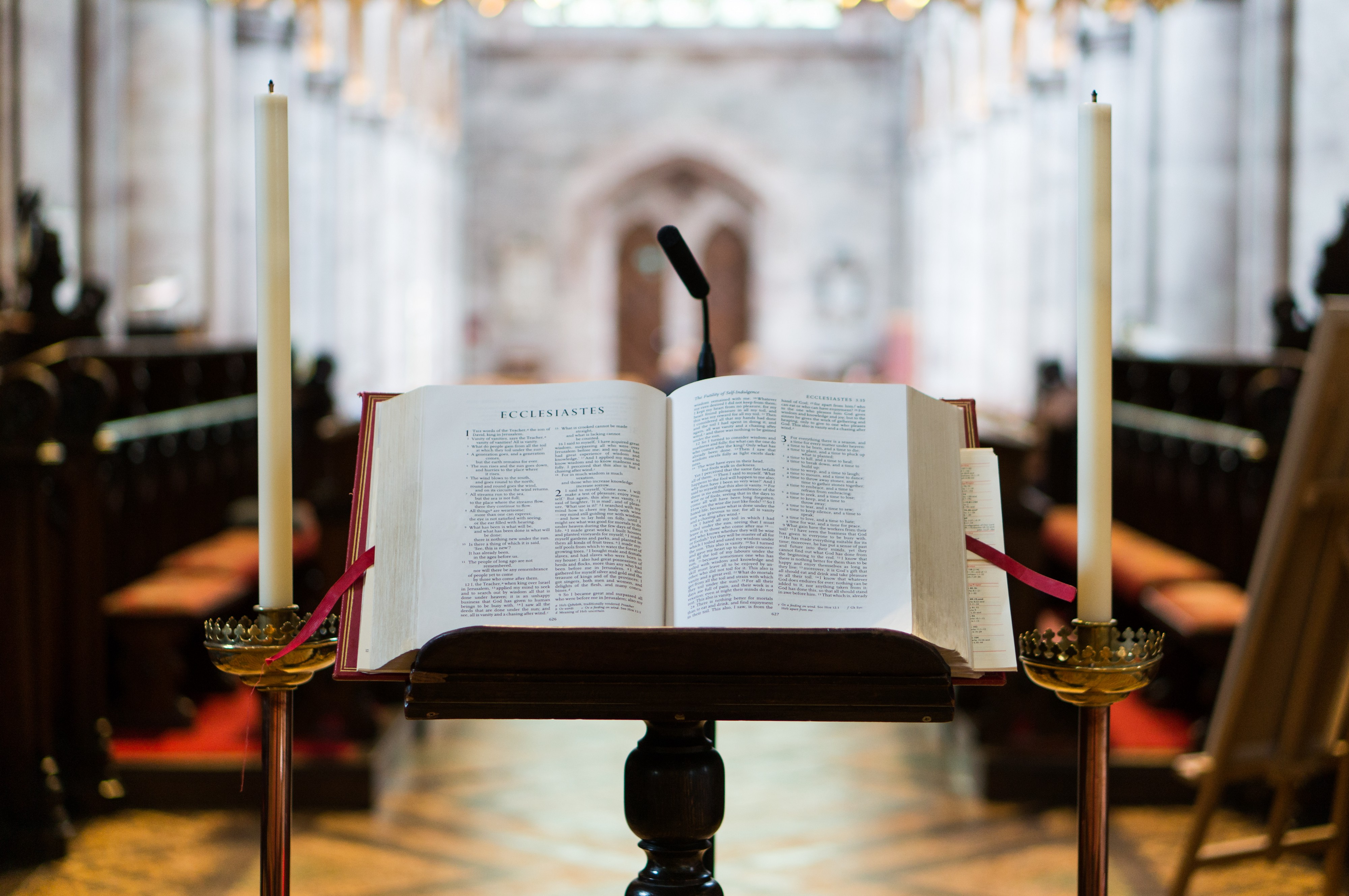 Photo of a Bible open on a pulpit in front of a church.