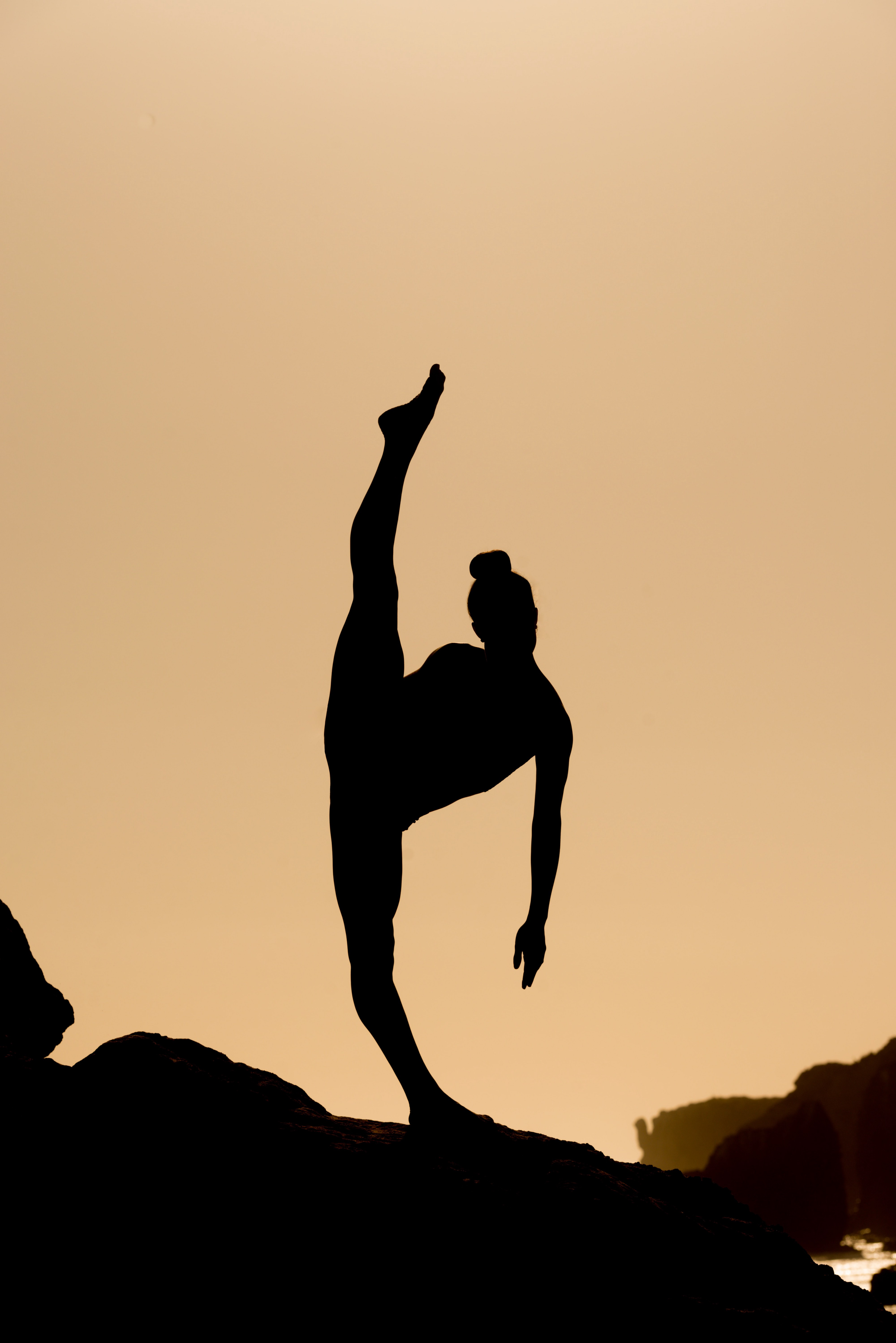 Sillhouette of person in front of amber background doing standing splits with ground leg (left leg) hyperextended.