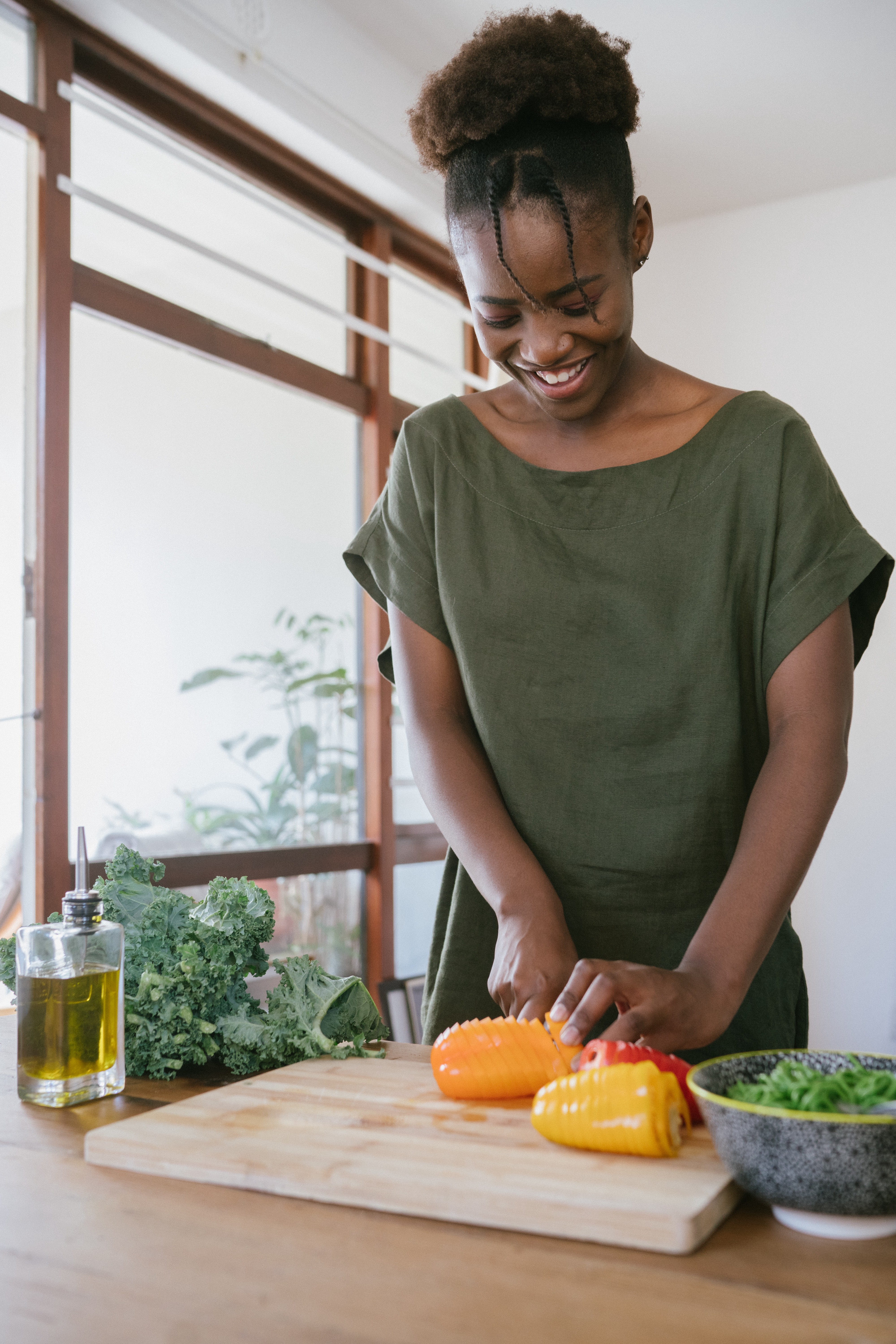 Smiling woman slicing peppers on cutting board