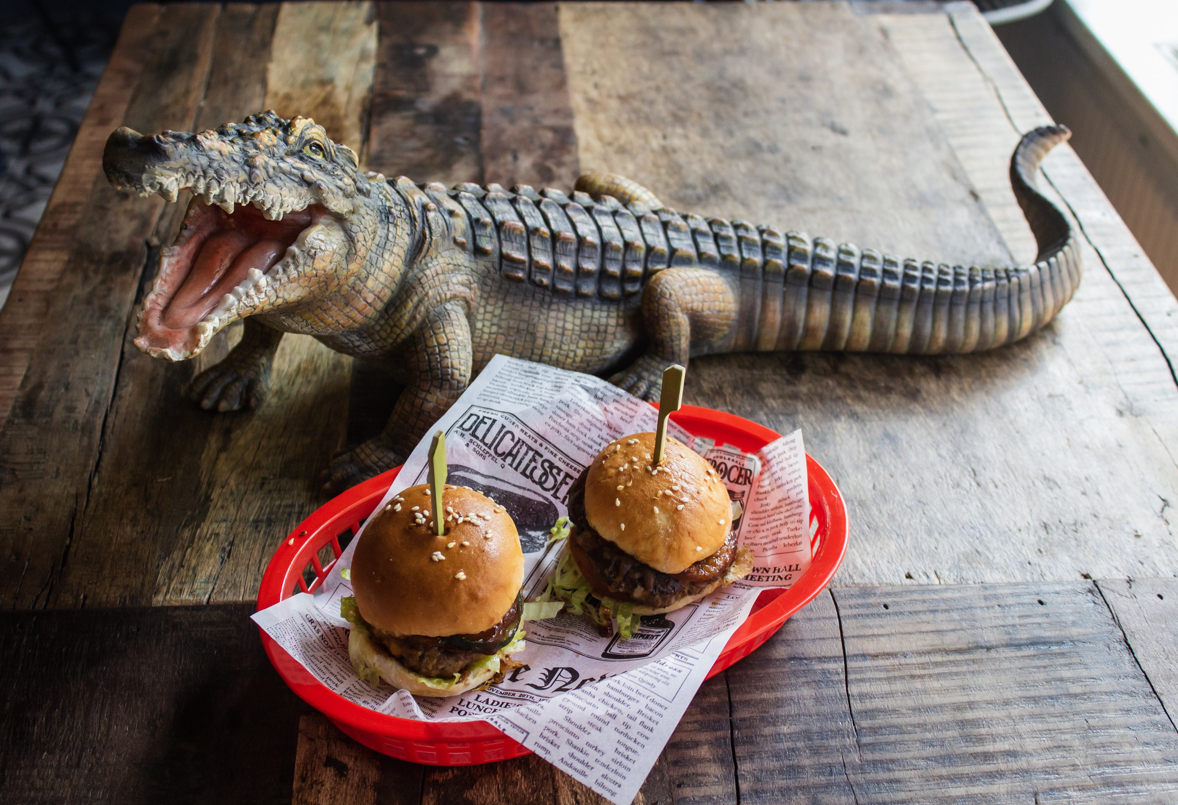 A couple of fresh burgers served in a red basket at a Louisiana bar. An alligator statue sits on the table with the burgers.