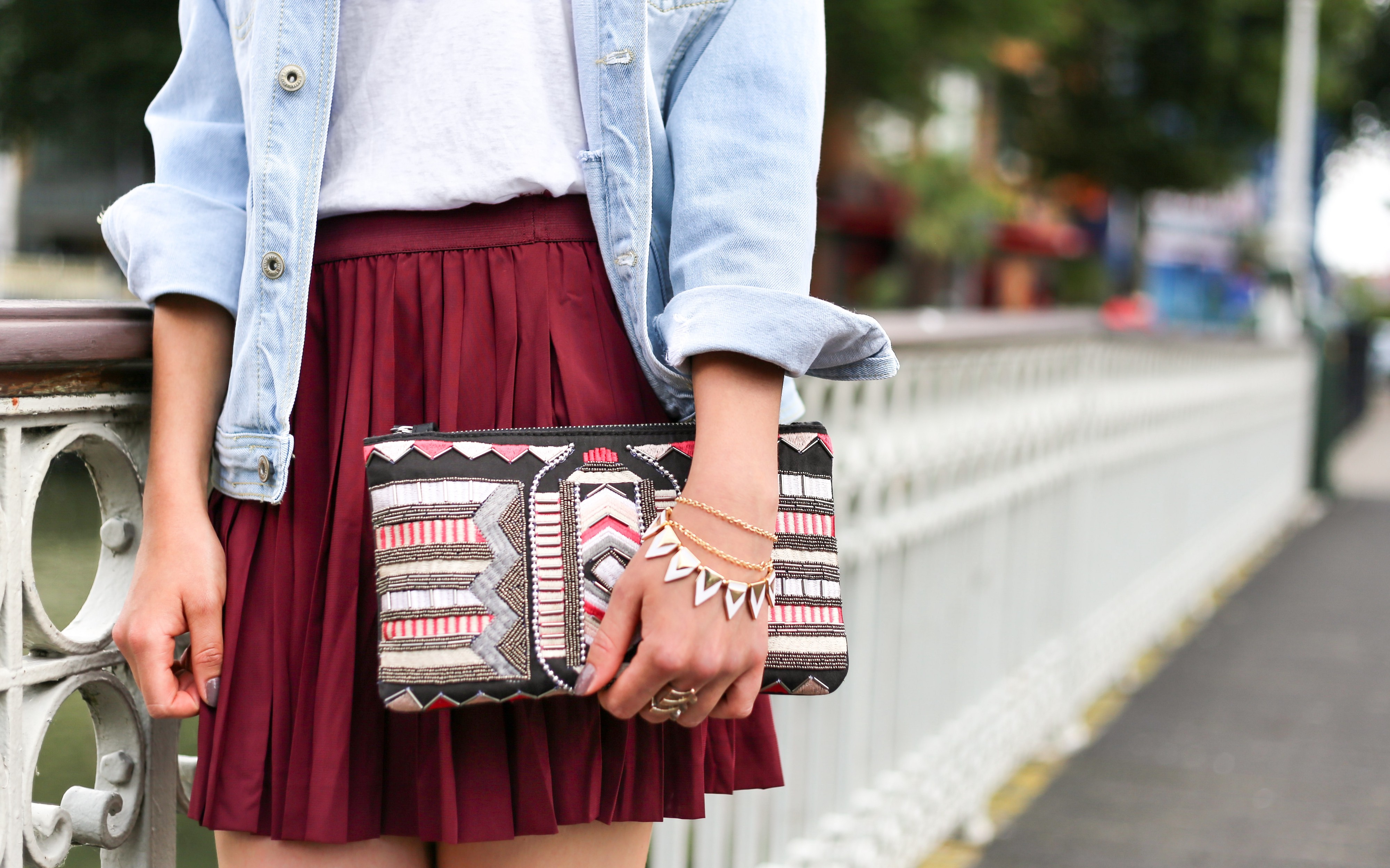 Middle of a person in a short, pleated, pocketless skirt, wearing bracelets and rings, and holding a strapless clutch purse.